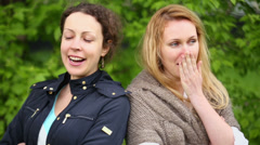 Two young woman look and yawn against green foliage Stock Footage