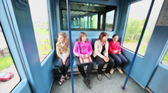 Four girl sit in train of monorail system during ride Stock Footage