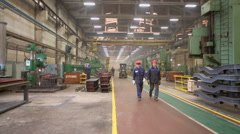 Workers walk and loader rides at workshop in factory Stock Footage