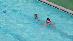Mother swimming with four years old child in pool Stock Footage