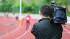 Operator with camera records sportsmen which run by track Stock Footage