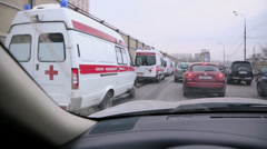 Motorcade of ambulance cars ride among traffic Stock Footage