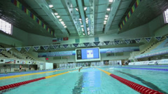 Several people swim by tracks in pool at Olympic Sports complex Stock Footage