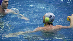 Water polo players pass ball during game in basin Stock Footage