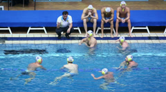 Coach talk with water polo team players at pool edge in basin - stock footage