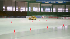 Tregubov and Vasilenko ride in yellow racing car on ice Stock Footage