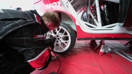 Stock Video Footage of Automobile mechanic screws wheel of race car of team ALM RUSSIA
