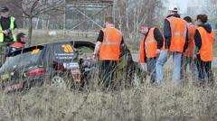 Journalists and servicemen work near broken race car Stock Footage