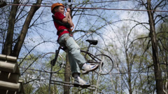 Boy descends from platform at tree on rope in climbing park Stock Footage