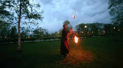 Woman runs and rotates poi with flame during fire show Stock Footage