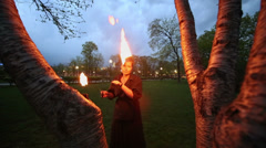 Woman  rotates poi with flame during fire show near birches Stock Footage