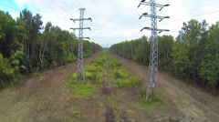 Power transmission towers in middle of forest during the day Stock Footage