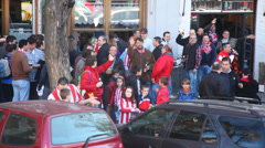 Football fans waving to the camera in front of a bar Stock Footage