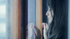 Sad girl near window thinking about something - stock footage