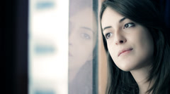 Pensive young woman looking through a window - stock footage