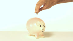 Man dropping coin in piggy bank - stock footage