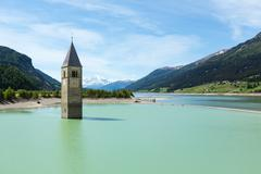 the bell tower in reschensee and family (italy). - stock photo