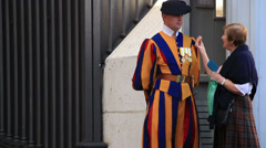 A Swiss guard at St Peters talk to a lady 2 Stock Footage