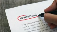 Circling Marketing with a red marker Stock Footage