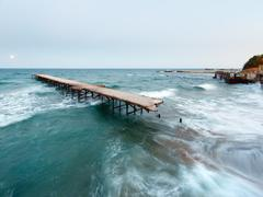 Evening sea surf, ruined pier and moon in sky (black sea, bulgaria). long-tim Stock Photos
