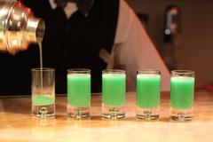 Stock Photo of barman serving green alcohol shots.