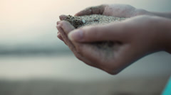 Sea sand running through a womans hands Stock Footage