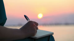 Woman writing in her diary at sunset Stock Footage