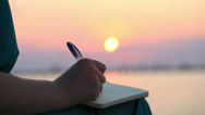 Stock Video Footage of Woman writing in her diary at sunset