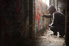 illegal young man spraying black paint on a graffiti wall. - stock photo