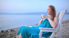 Woman enjoying a cup of tea at the seaside Stock Footage