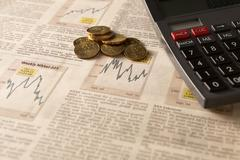 Newspaper stock market with calculator and money Stock Photos