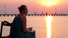 Young woman writing in her diary by the seashore Stock Footage