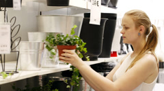 Young blond woman looking at vases with plants in a shop Stock Footage