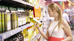 Young woman buying olive oil Stock Footage