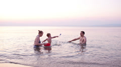Young family playing red toy boat at sunset - stock footage