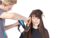 woman enjoying having her hair blow dried - stock photo