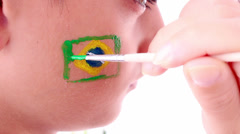 Boy face painting flag of Brazil - stock footage