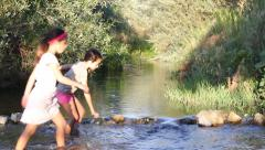 Two Girls Cross a Creek Stock Footage
