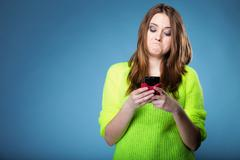 Funny girl with mobile phone reads message Stock Photos