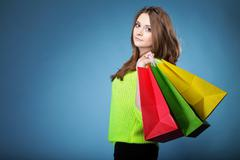 young woman with paper multi coloured shopping bag - stock photo