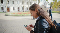 Woman tourist is looking for an address with a GPS navigator on a smartphone Stock Footage