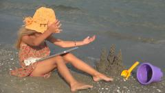 Child playing on Tablet on the Beach Stock Footage