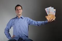 man with piggy bank and euro banknote - stock photo