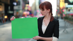 Caucasian business woman in New York City street holding message board Stock Footage