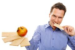 Healthy lifestyle man eating crispbread and apple Stock Photos