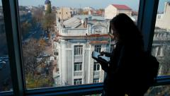 girl tourist near a window with tablet computer - stock footage