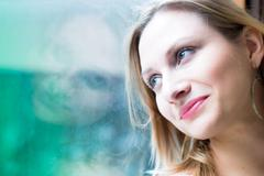 Woman standing by a window looking outside Stock Photos