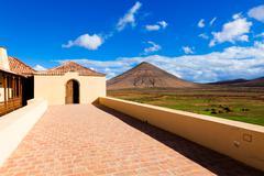 volcano montana oliva and historical building casa de los coroneles, la oliva - stock photo
