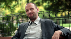 Portrait of young happy, smiling businessman sitting on bench in park HD Stock Footage