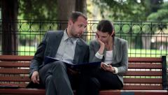 Overwhelmed business people working with documents, solving problem on bench HD Stock Footage